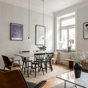 A Scandinavian inspired living room with grey walls and big windows. This dreamy Swedish apartment has the right balance between functionality and style. By looking at this, you will find out all the tips you need to find out how to decorate a small apartment.