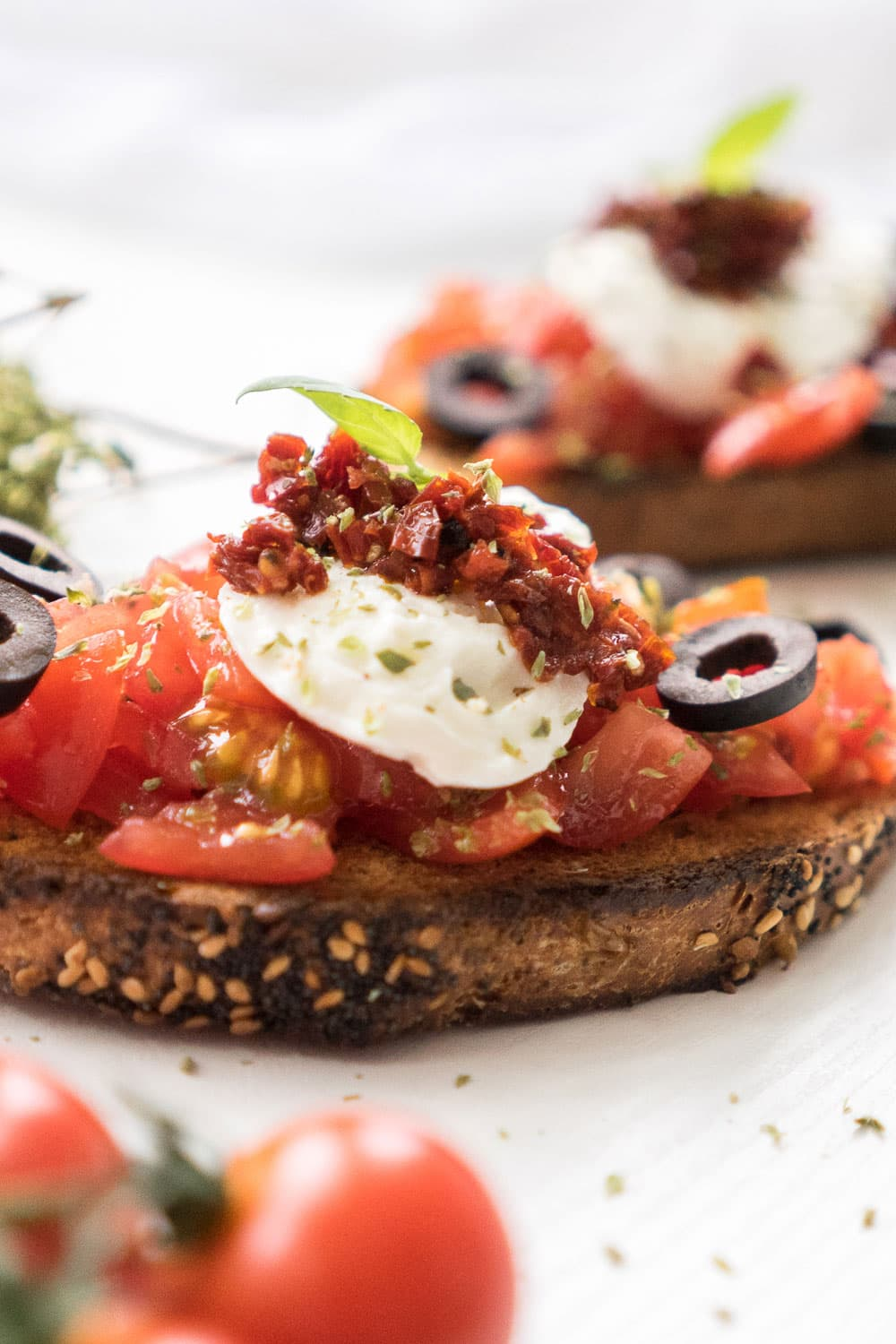 This perfect grilled bruschetta with mozzarella and tomatoes recipe will make your summer BBQ special! Grilled smoky bread, delicious sun-ripened tomatoes, sun-dried tomatoes, extra virgin olive oil, delicious mozzarella and black olives make this the ultimate appetizer for your summer parties!