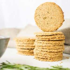 Homemade healthy oatcakes on a white surface with rosemary in front of them.