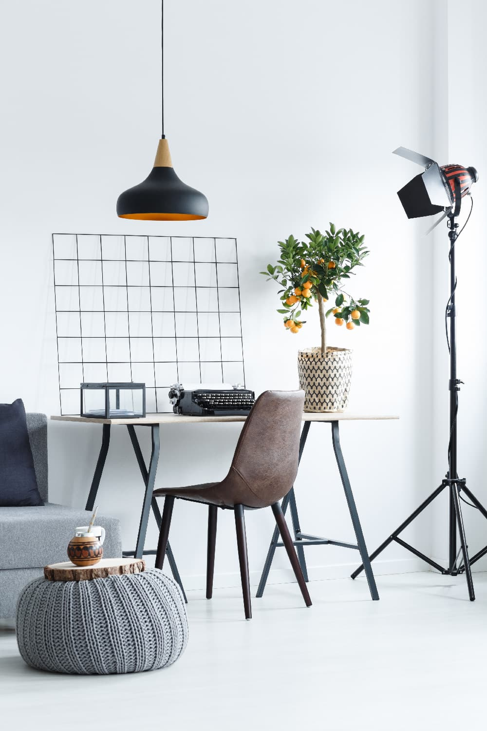 View of a modern office with a leather chair and a small orange tree on a wooden desk: the perfect corner to make money from home.