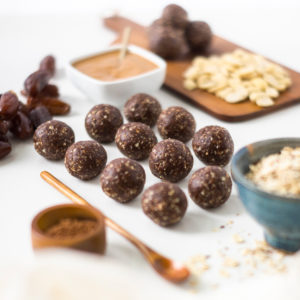 No-bake peanut butter balls on a white surface surrounded by oats and cocoa powder.