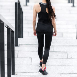Woman walking down stairs in gym clothes, testing the sweatccoin app