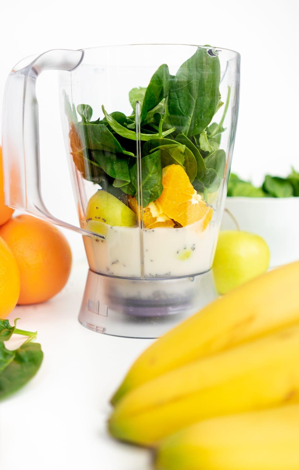 Green smoothie ingredients in a blender: spinach, orange, banana, chia seeds, green apple, oat milk