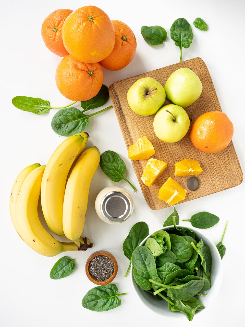 Healthy green smoothie ingredients top view: banana, spinach, oat milk, green apples, oranges