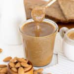 Spoon dipped in a glass jar filled with almond butter