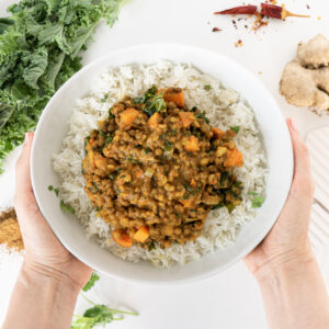 Top view of hands holding a white plate with coconut lentil curry and basmati rice.