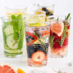 A picture of 6 glasses with infused water of different flavours on white background.