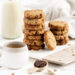 Side view of a pile of breakfast cookies with coffe and milk