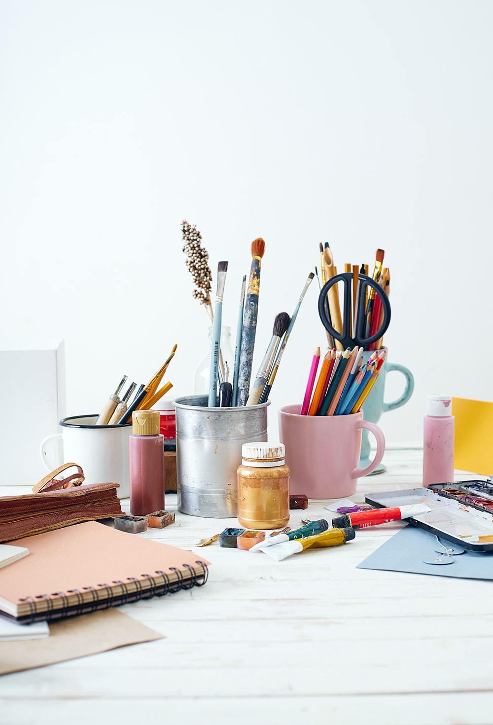 Art supplies on a desk including pencils. brushes, paper: to inspire you to find ways to make money with art
