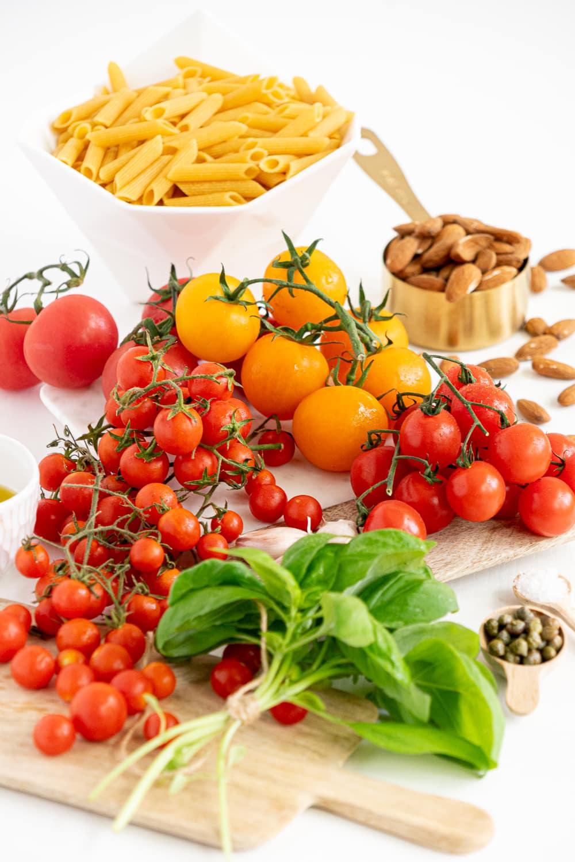 Uma visão aérea de todos os ingredientes necessários para fazer uma pasta de tomate cremosa sem ferver: tomates frescos, manjericão fresco, alho, azeite de oliva extra virgem, amêndoas, alcaparras, sal, macarrão.