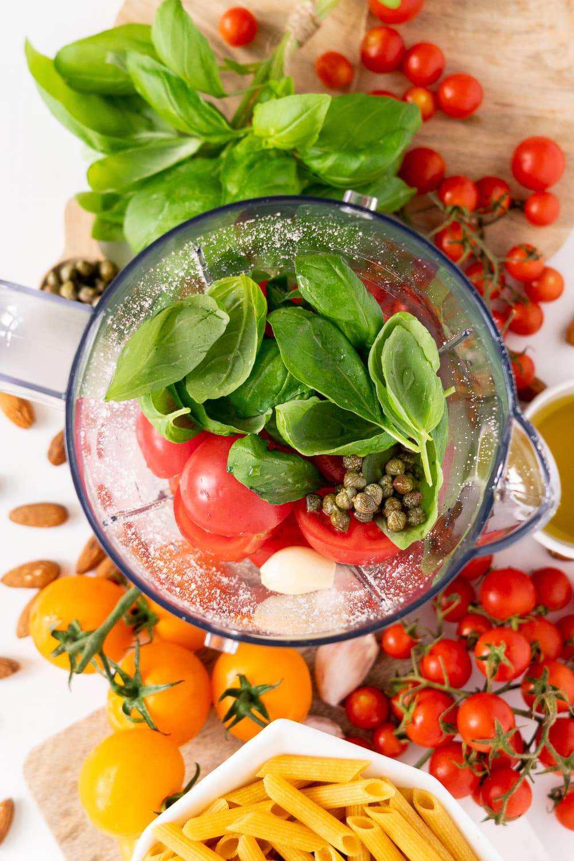 Vista superior do liquidificador com manjericão, tomate, alho, alcaparras, azeite e amêndoas dentro, cercado por tomates e manjericão