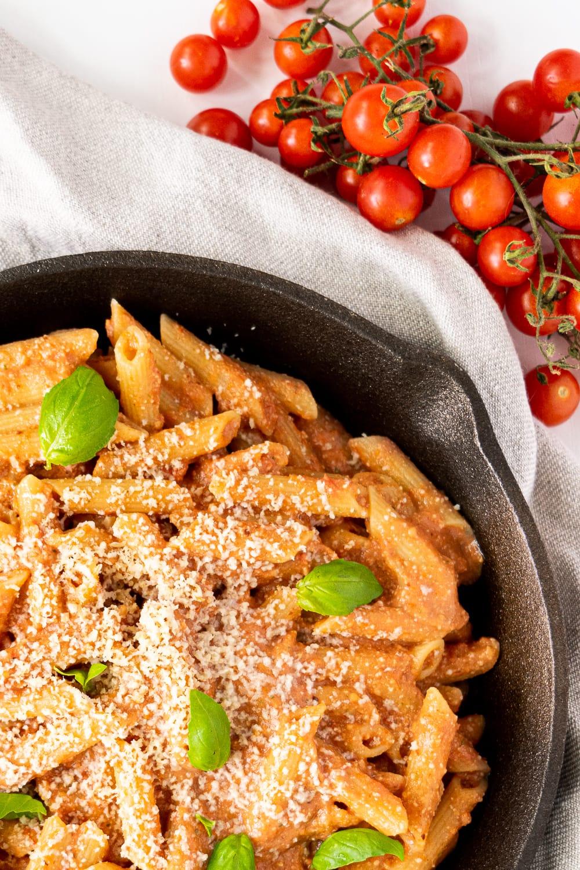 vista superior de uma frigideira de ferro com pasta de tomate cremosa com folhas de manjericão e parmesão vegan