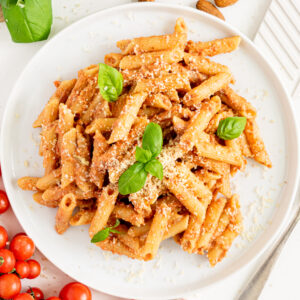 top view of white plate with creamy tomato pasta topped with basil leaves and vegan parmesan