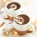 Three quarter view of healthy hot chocolate mugs with coconut whipped cream and cacao nibbles
