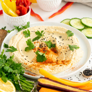 Easy hummus recipe on a white plate with veggies