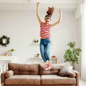 Woman jumping on a sofa happy to find out how to make $1000 a month