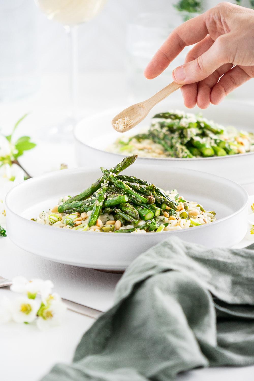 Hand putting vegan parmesan on asparagus risotto