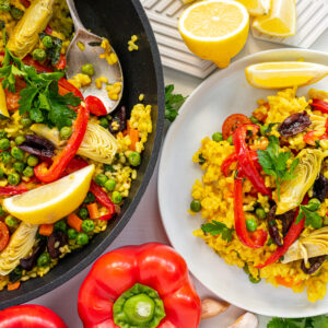 Top view of a plate and a pan filled with vegetarian paella